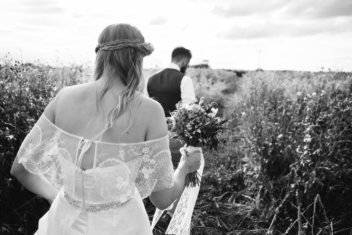 country wedding couple walking in a field